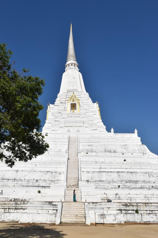 Templo muy alto en forma triangular con una gran escalinata. Chica de pie en la escalinata. Todo el templo es blanco a excepción de una puerta al final de la escalinata que es dorada.