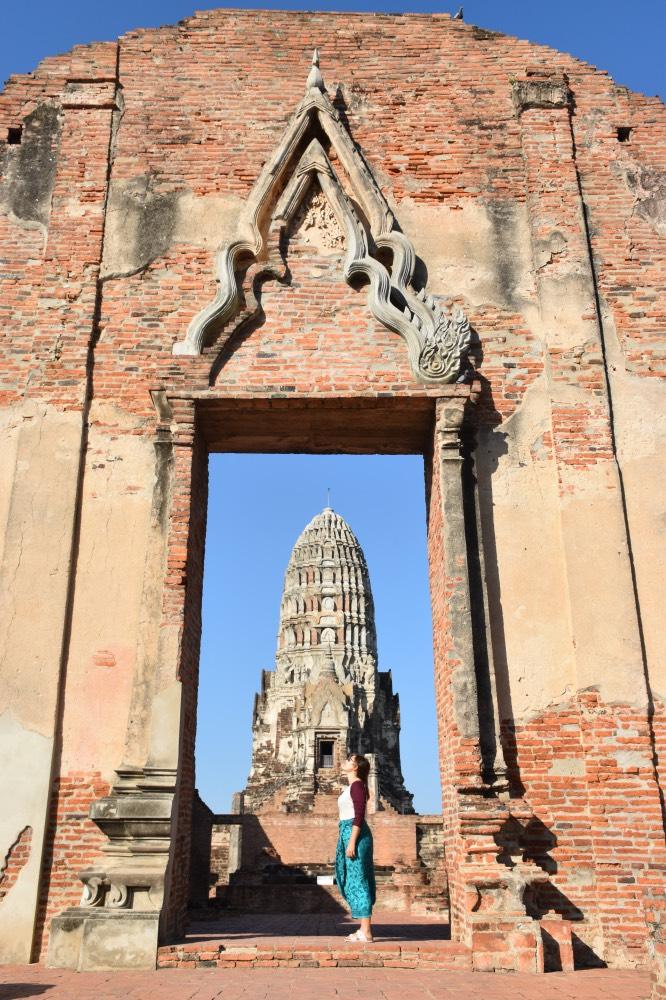 Un día en Ayutthaya: Chica en el centro de una puerta de ladrillos en ruinas y, de fondo, un prang, la columna central de un templo.
