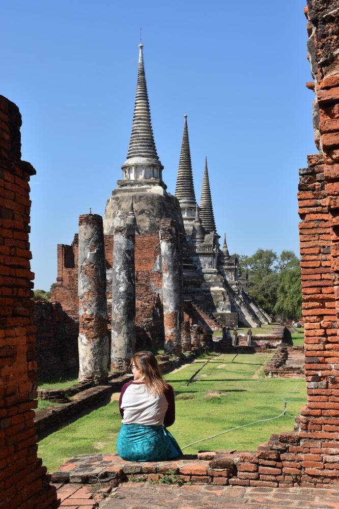 Chica sentada en unas ruinas, de fondo se ven columnas y tres grandes estupas iguales
