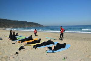 Hacer surf en Galicia - estiramientos en la arena antes de hacer surf