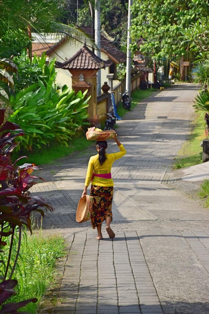 Mujer balinesa con el traje típico. En la cabeza lleva una cesta con ofrendas para el templo.