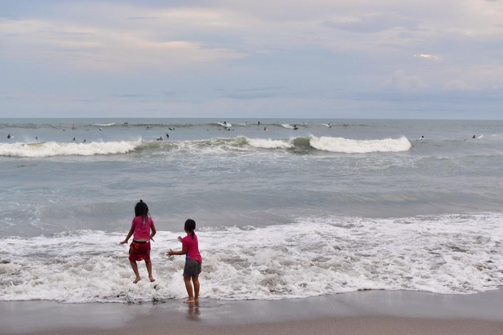 Niñas jugando en el agua. Al fondo, decenas de surferos