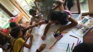 Los niños del centro preparando la pancarta