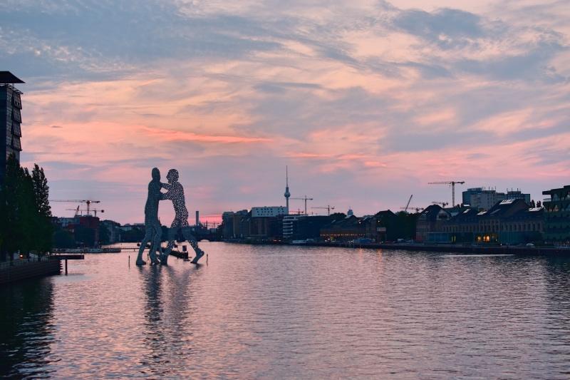 Cosas que hacer en Berlín: escultura de dos hombres gigantes en el río al atardecer