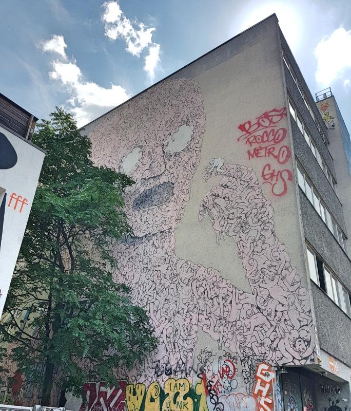 Los mejores grafitis de Berlín: hombre de color rosa comiendo a un hombre