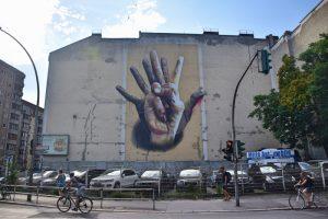 Los mejores grafitis de Berlín: una mano negra y una mano blanca dibujadas en la pared de un aparcamiento