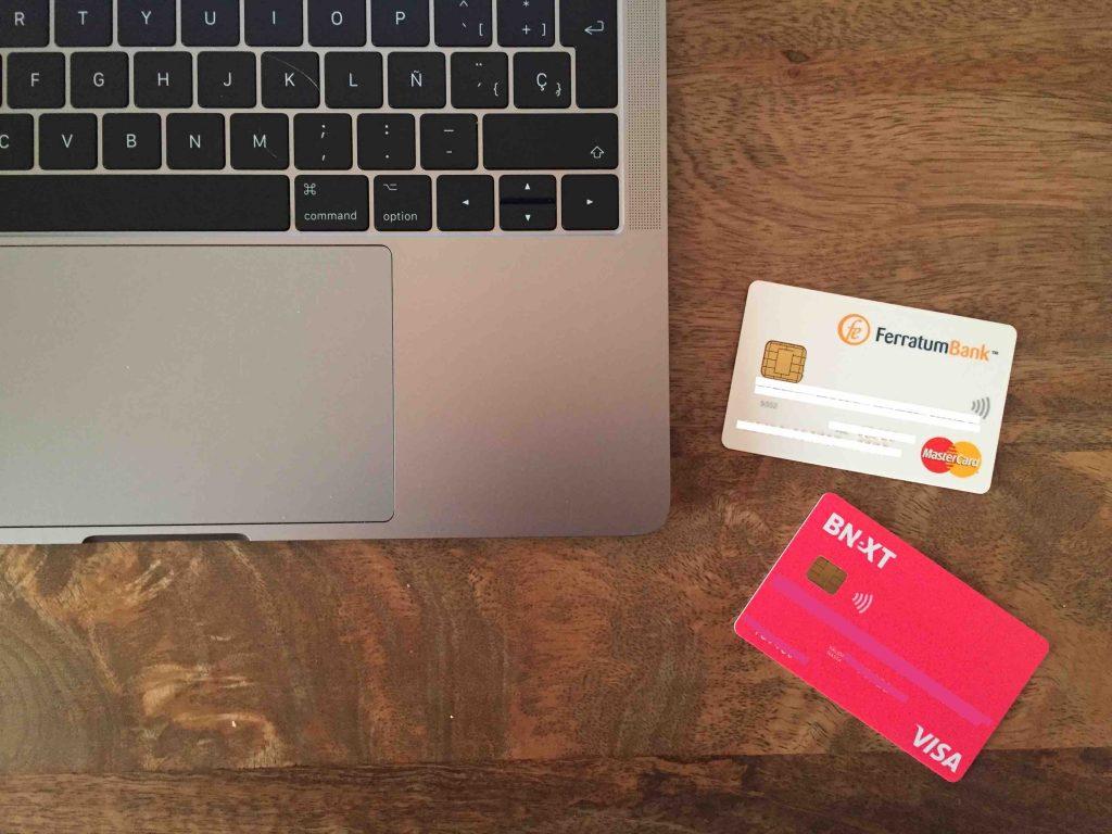 Tarjetas Ferratumbank y BNEXT junto con MacBook Pro encima de escritorio de madera.