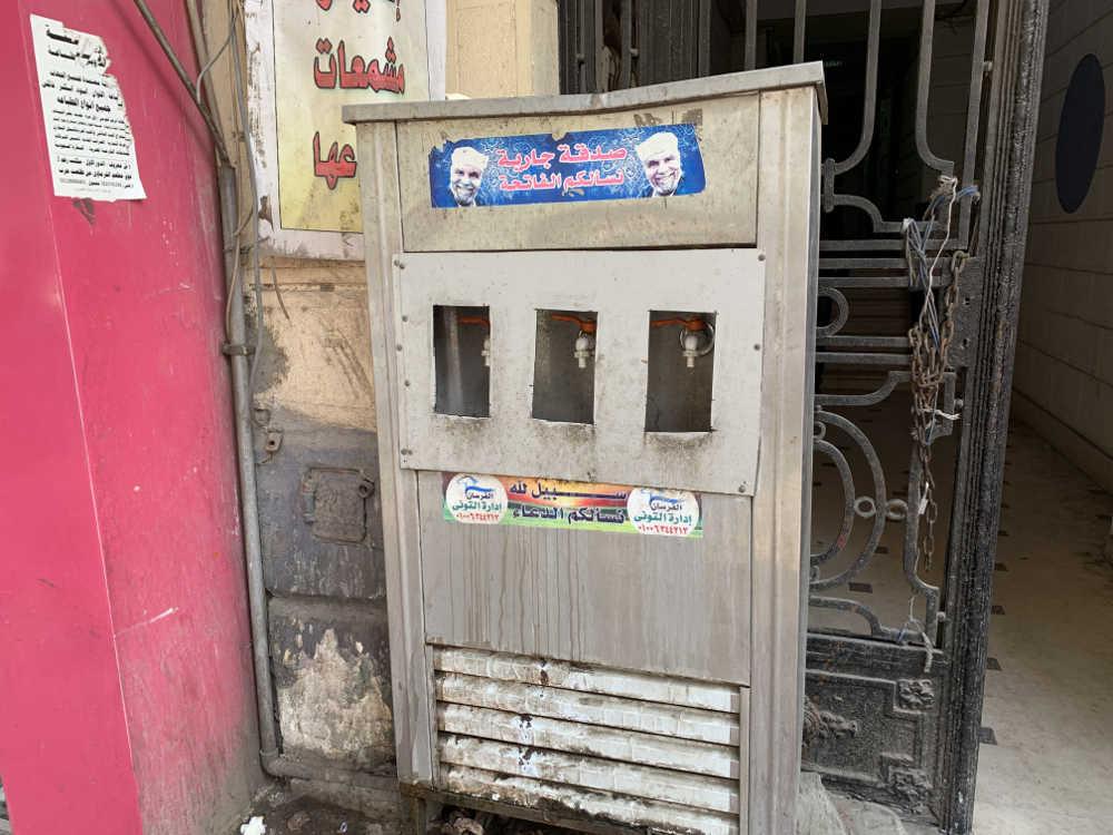 maquina de agua callejera en El Cairo con tres grifos, metálica y sucia