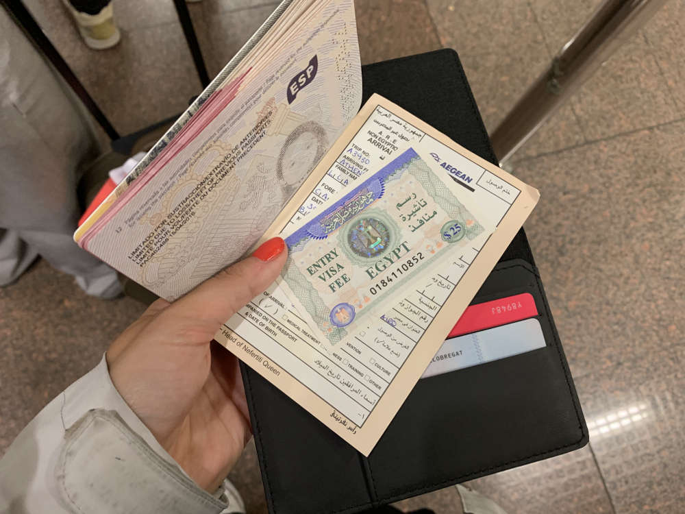 carla coge con la mano su pasaporte con el visado de egipto y la tarjeta de inmigración