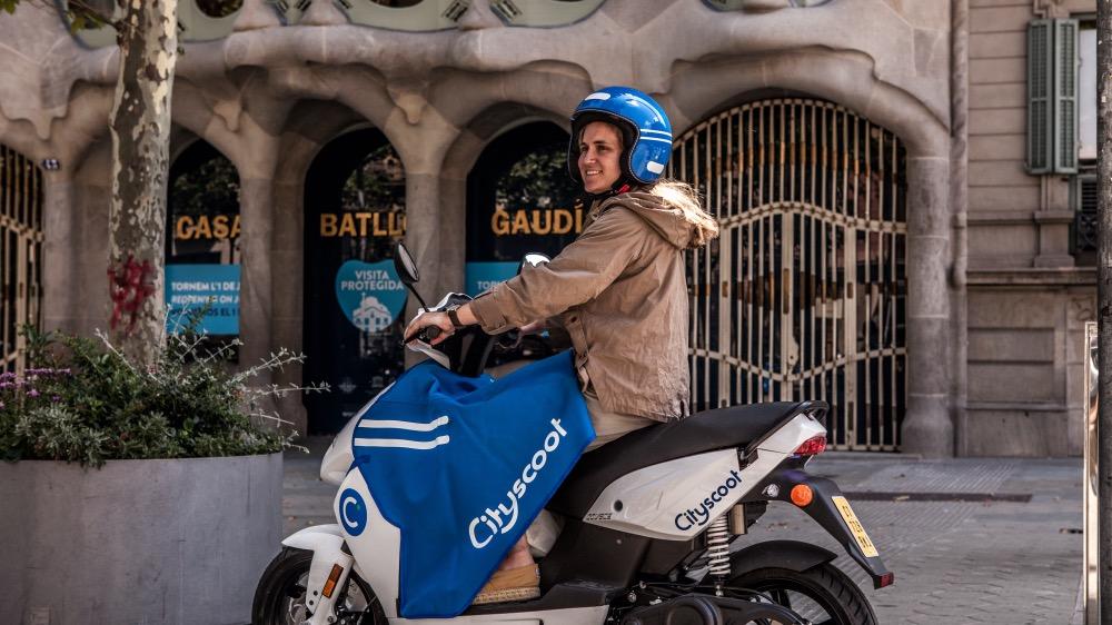 Chica sobre una moto marca cityscoot frente a la Casa Batlló de Barcelona