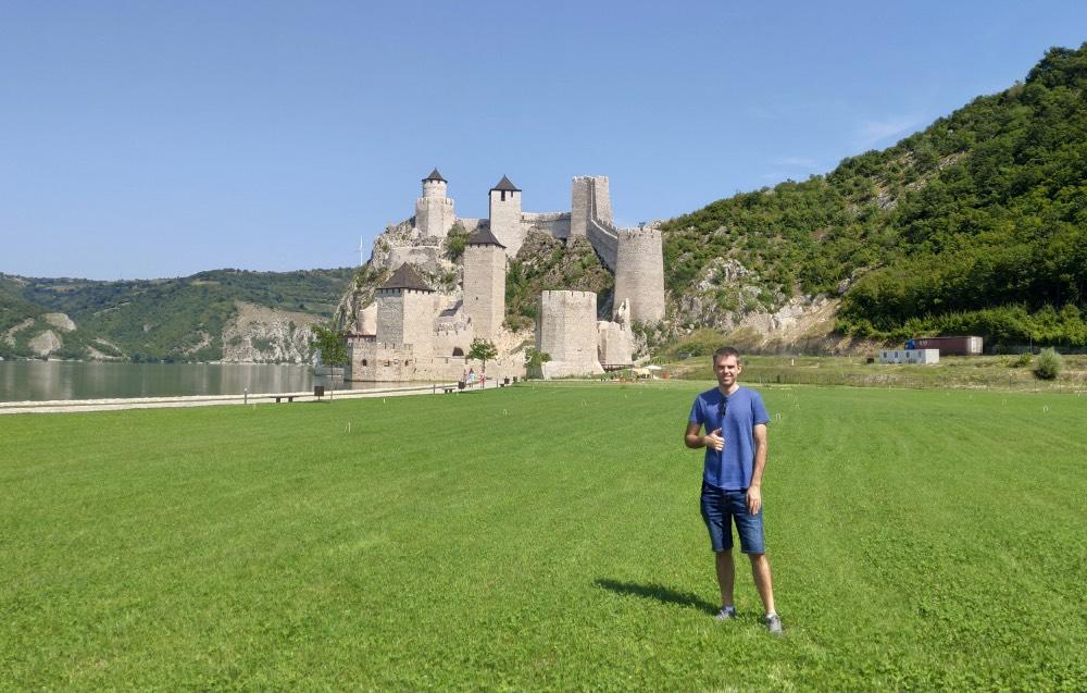 Joaquín en un prado verde con un castillo de fondo y un lago.