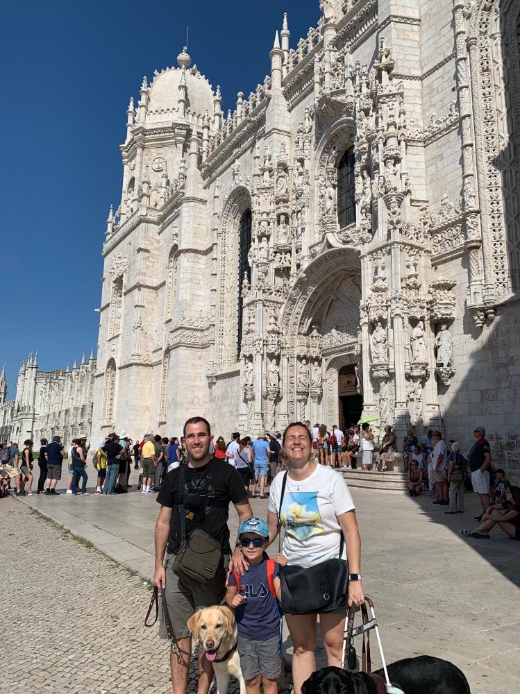 Viajar siendo ciegos: Núria y Juanjo con su hijo Eric, los dos perros guías y, de fondo, una catedral.