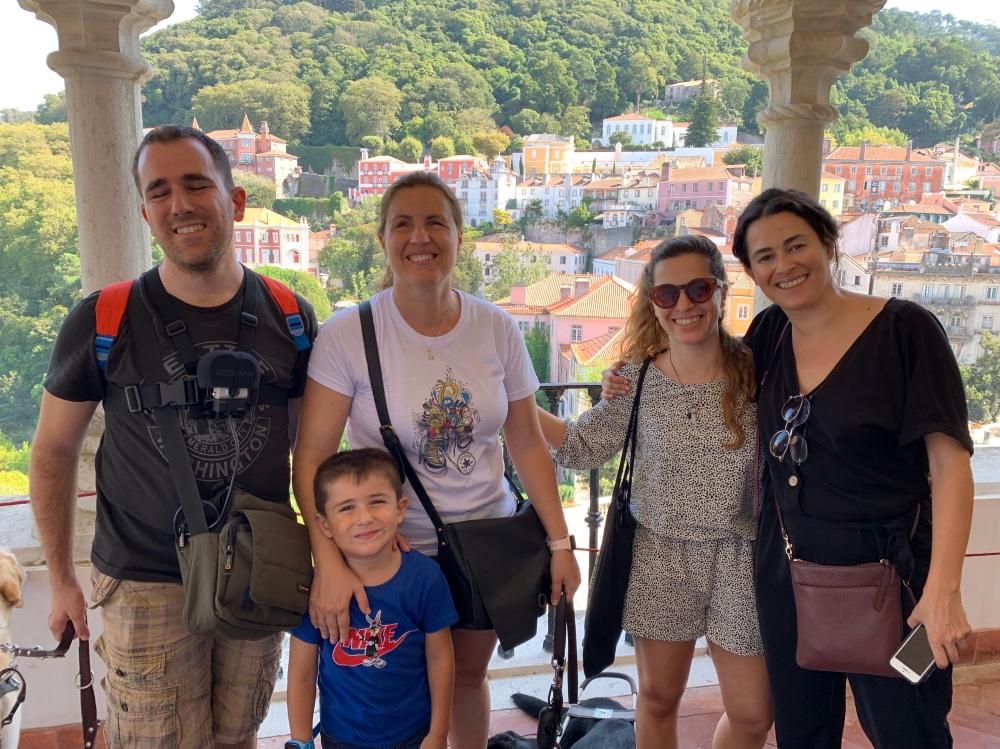 Viajar siendo ciegos. Núria y Juanjo con su hijo y dos mujeres, de fondo un paisaje de casitas.