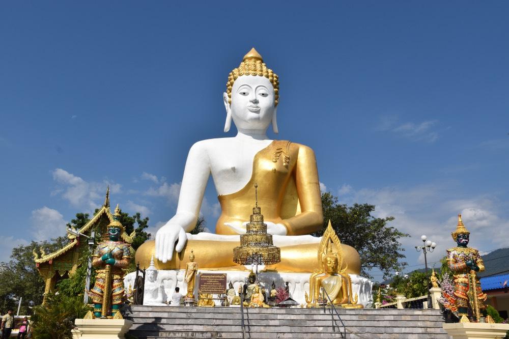 Buda gigante sentado, de color dorado y blanco y con una escalinata delante.
