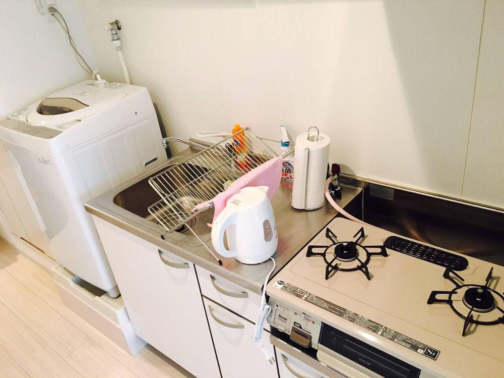 buscar alojamiento en Japón: Cocina pequeña con lavadora, fregadero, armarios inferiores, dos fogones de gas, horno. Se ve escurreplatos, calentador de agua y rollo de papel. Suelo, pared y cocina blanco.