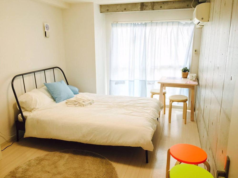 buscar alojamiento en Japón: Habitación de piso japonés con ventana y balcón al fondo, cortina blanca, cama grande con nórdico blanco, cabecero de hierro negro sencillo, mesita y banquetas de madera, suelo de madera, aire acondicionado, paredes blancas.