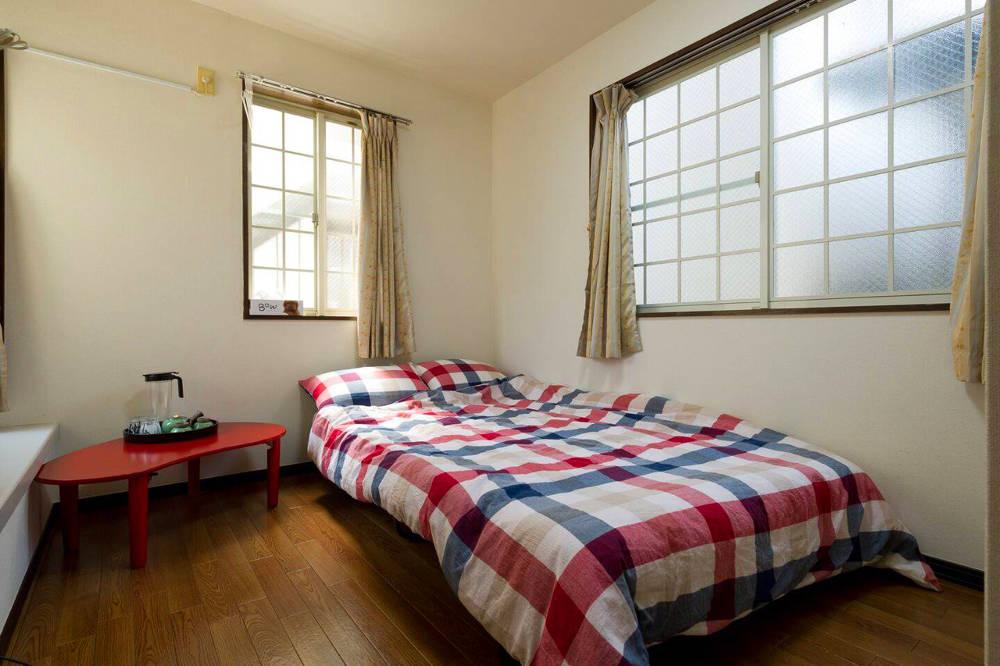 buscar alojamiento en Japón: Habitación con suelo de madera, mesita roja con kit de té, cama en la esquina con colcha cuadros de rayas azules y rojas, dos ventanas grandes, pared blanca.