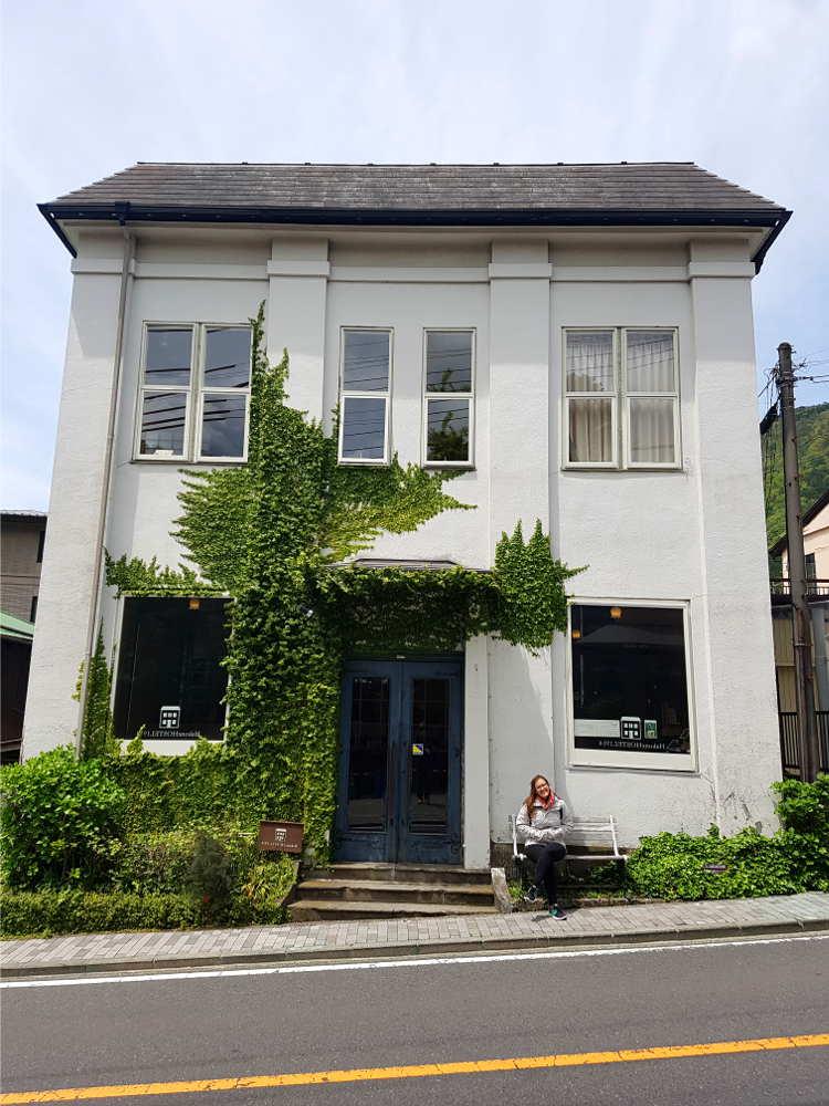 Edificio de hostel blanco de dos plantas, tejado gris oscuro y planta enredadera en un lado de la pared. Tiene cinco ventanas y la puerta principal. Se encuentra a pie de carretera y la acera es estrecha.