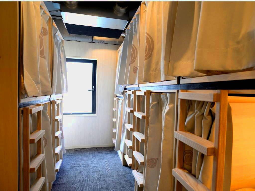 Habitación de hostel, pasillo de moqueta azul, a ambos lados literas dobles de madera cerradas por cortinas blancas. Al fondo pared blanca con ventana.
