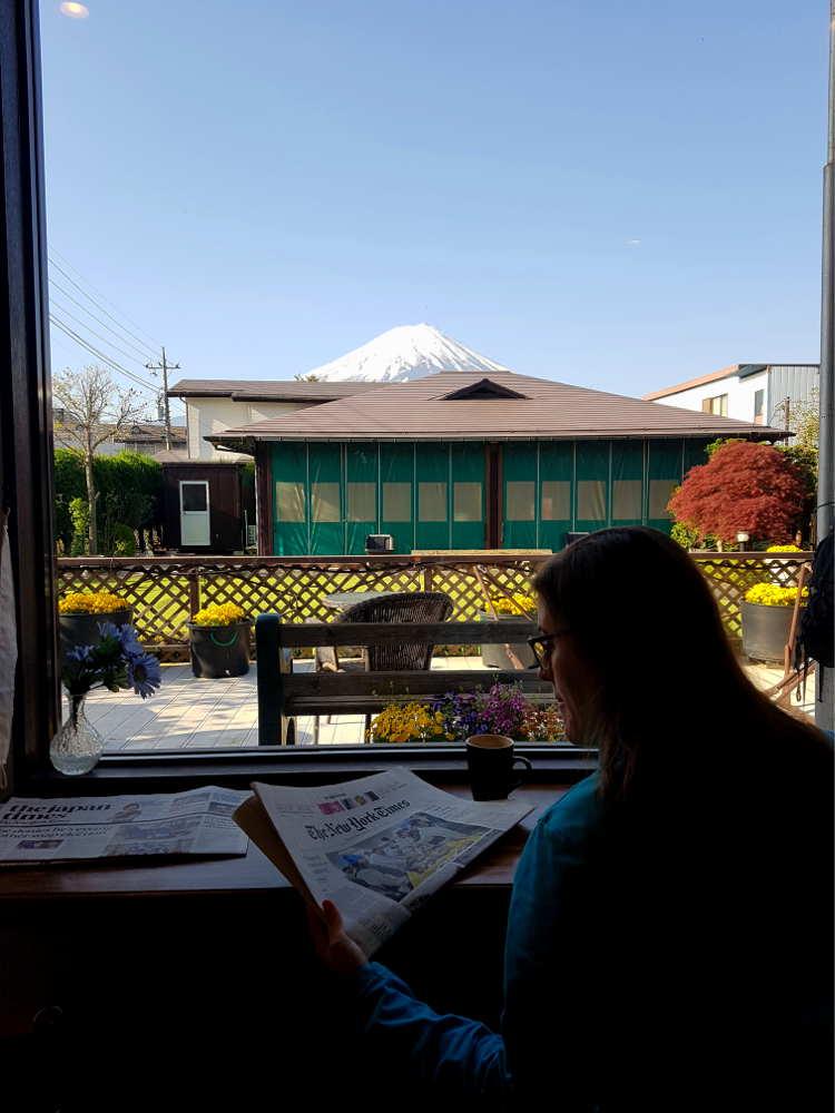 Carla lee el periódico y toma un té sentada frente a una ventana con vistas a la terraza, a una casa y al monte Fuji.