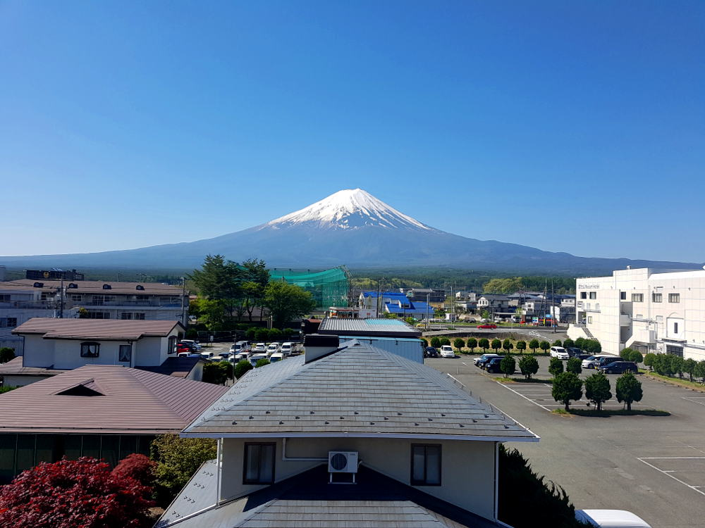 Cielo azul despejado con el monte Fuji al fondo viéndose muy cerca. Por debajo se ven los tejados de las casas del pueblo y un aparcamiento.