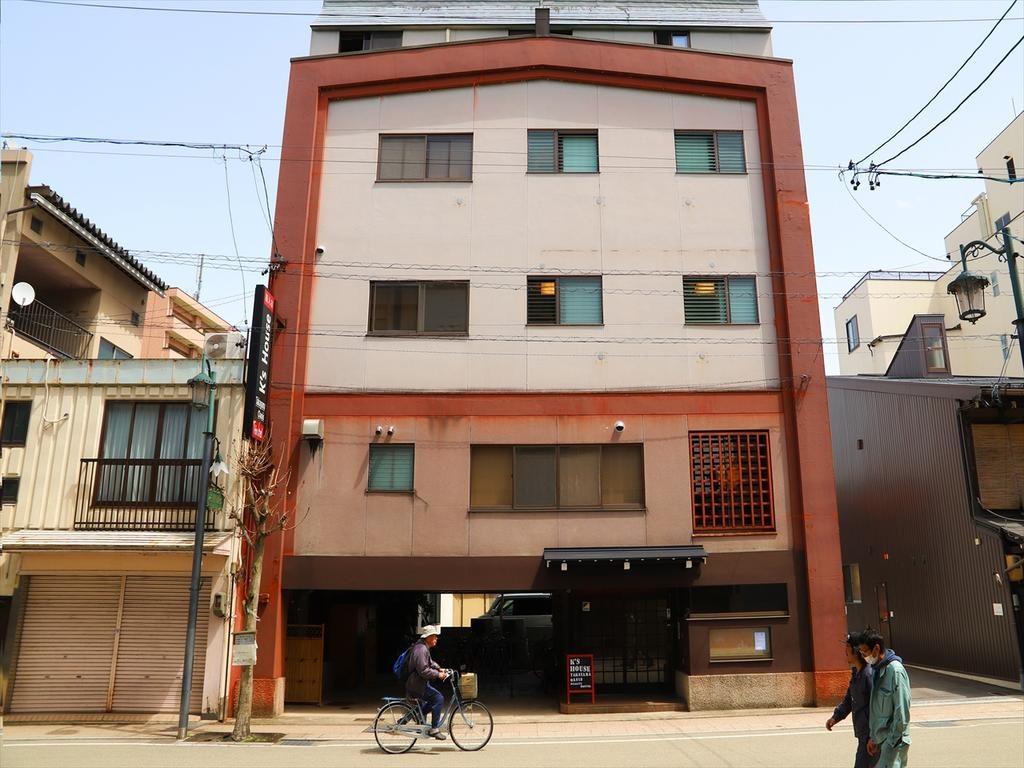buscar alojamiento en Japón: Edificio del hostel de color rojizo con gente paseando por la calle.