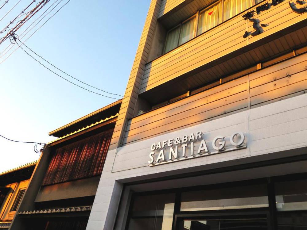 Fachada del hostel al atardecer, cielo azul y colores cálidos, fachada de madera con cartel que pone café y bar Santiago.