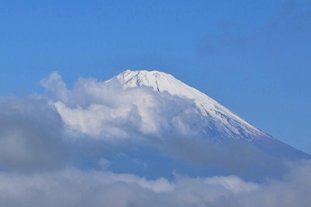 punta del monte Fuji nevada, color azul de cielo y nubes en la parte baja, por la mañana