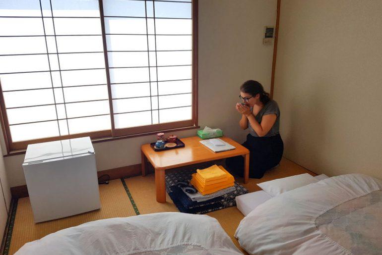 Habitación tradicional japonesa, suelo de bambú, ventanas de madera y papel blanco traslúcido, fotones blancos, nevera pequeña y mesita con bandeja de té. Carla de rodillas con ambas manos coge un vaso de té y se lo lleva a la boca.