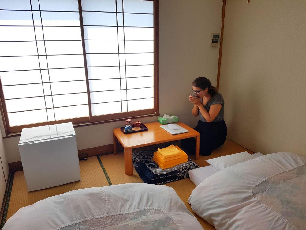 buscar alojamiento en Japón: Habitación tradicional japonesa, suelo de bambú, ventanas de madera y papel blanco traslúcido, fotones blancos, nevera pequeña y mesita con bandeja de té. Carla de rodillas con ambas manos coge un vaso de té y se lo lleva a la boca.