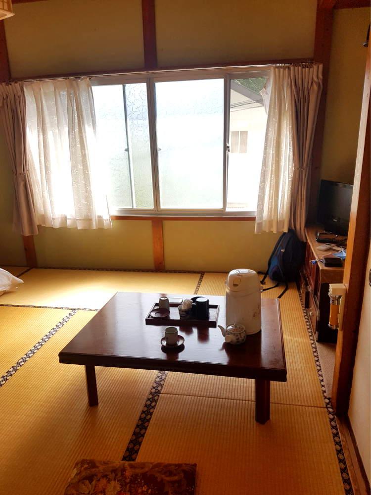 Habitación de madera en ryokan con suelo de bambú, mesita de madera corta con ceremonia de té en la mesa. Al fondo ventanal por con cortinas por donde entra la luz.