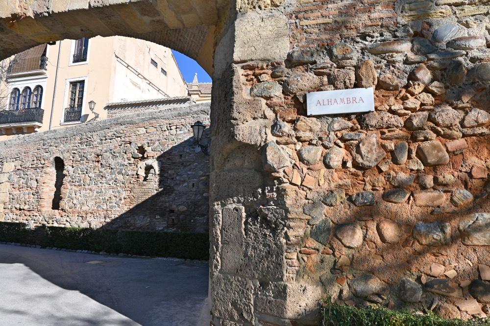 Cartel con la palabra 'Alhambra' junto a un arco de piedra que hace las veces de puerta