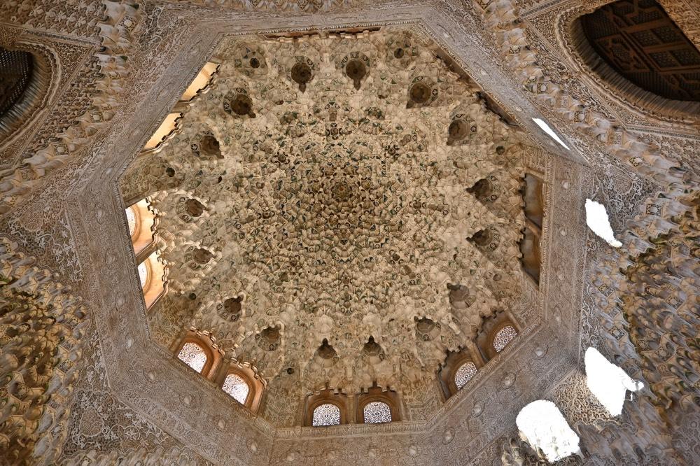 Visitar la Alhambra de Granada: techo decorado con motivos geometricos en tonos marrones y blancos.