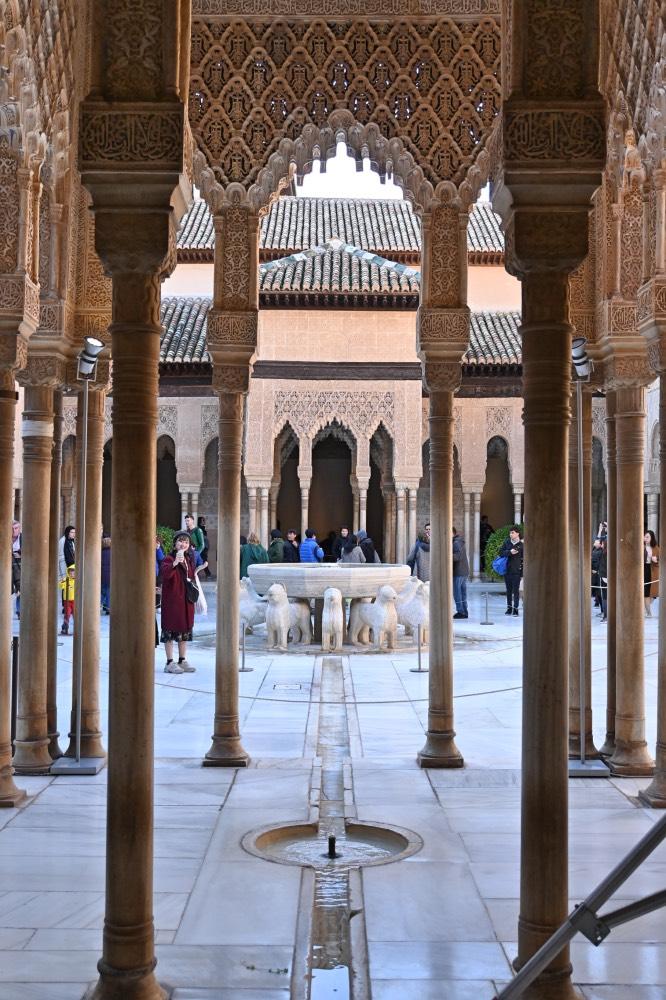 Visitar la Alhambra de Granada: patio de estilo árabe con una fuente en el centro y esculturas de leones alrededor.