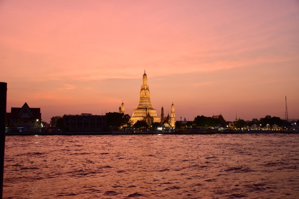 Cosas que hacer en Tailandia: atardecer color rosado con el Wat Arun, templo iluminado, y el río.