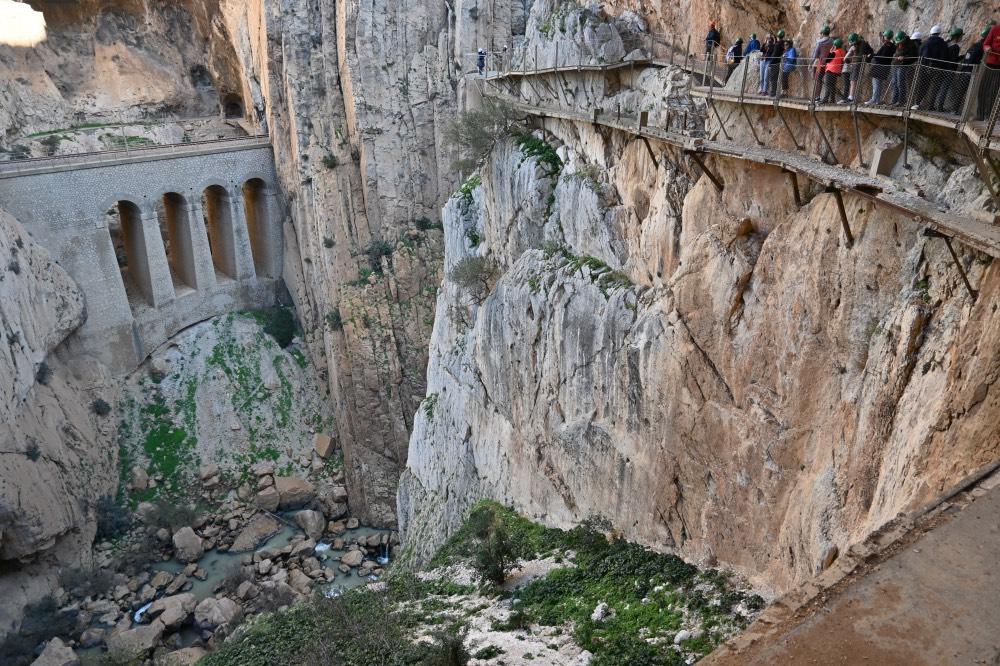 Hacer el Caminito del Rey en Málaga: Imagen del desfiladero. En el lado derecho, grupo de gente sobre una de las pasarelas nuevas. Se ve un tramo de la pasarela antigua justo debajo. Al otro lado del desfiladero, la vía del tren.