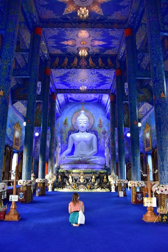 Cosas que hacer en Tailandia: templo azul, paredes azules, buda azul y yo sentada en el centro de espaldas a la cámara.