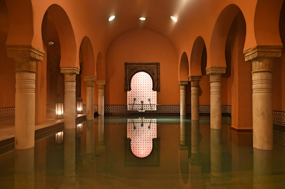 Piscina del Hammam al-Ándalus con columnas de estilo árabe. Iluminación tenue y velas.