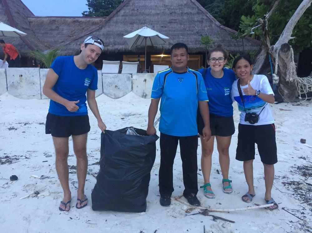 Nosotros y dos personas locales aguantando una bolsa de basura en la playa