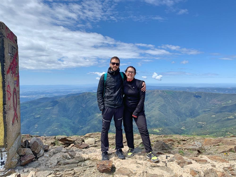 escapadas desde Barcelona: Adrián y yo vestidos de deporte y, de fondo, un paisaje de valles y montañas. Cielo azul y alguna nube.