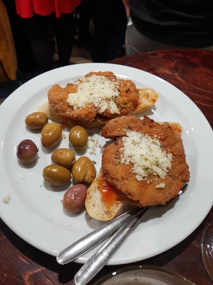 Dónde comer en Granada bien y barato: tapa de hamburguesa de pollo rebozado sobre pan, acompañada de aceitunas.