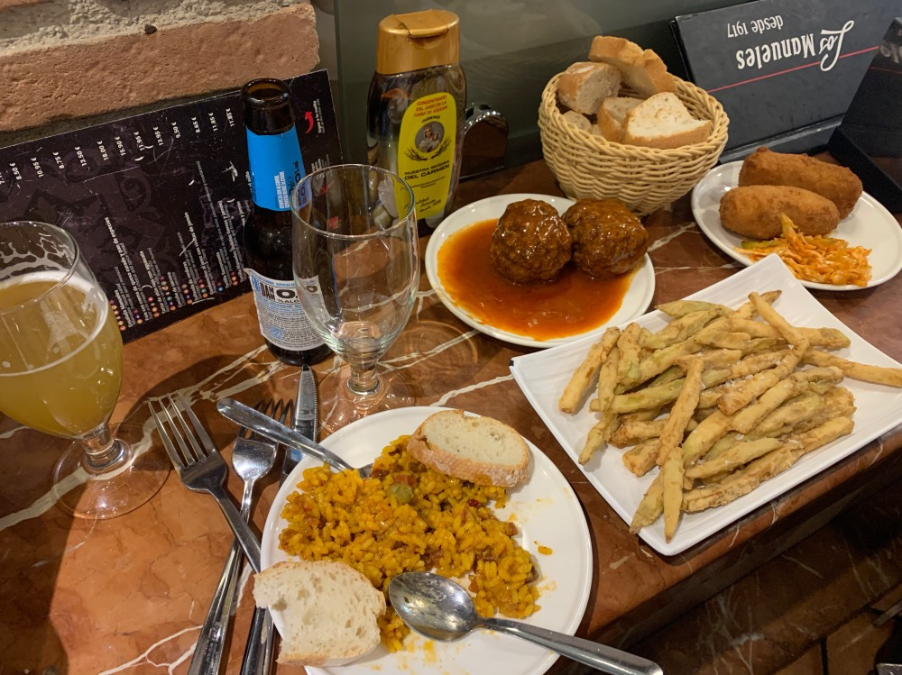Dónde comer bien y barato en Granada: diferentes tapas en una mesa (paella, berenjenas rebozadas con miel, croquetas, albóndigas en salsa) y una cerveza sin alcohol.
