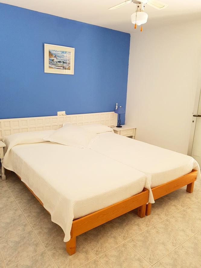 habitación con pared azul con cuadro marino y otra pared blanca, dos camas individuales juntas con sábanas blancas y pequeñas mesitas, suelo de mármol
