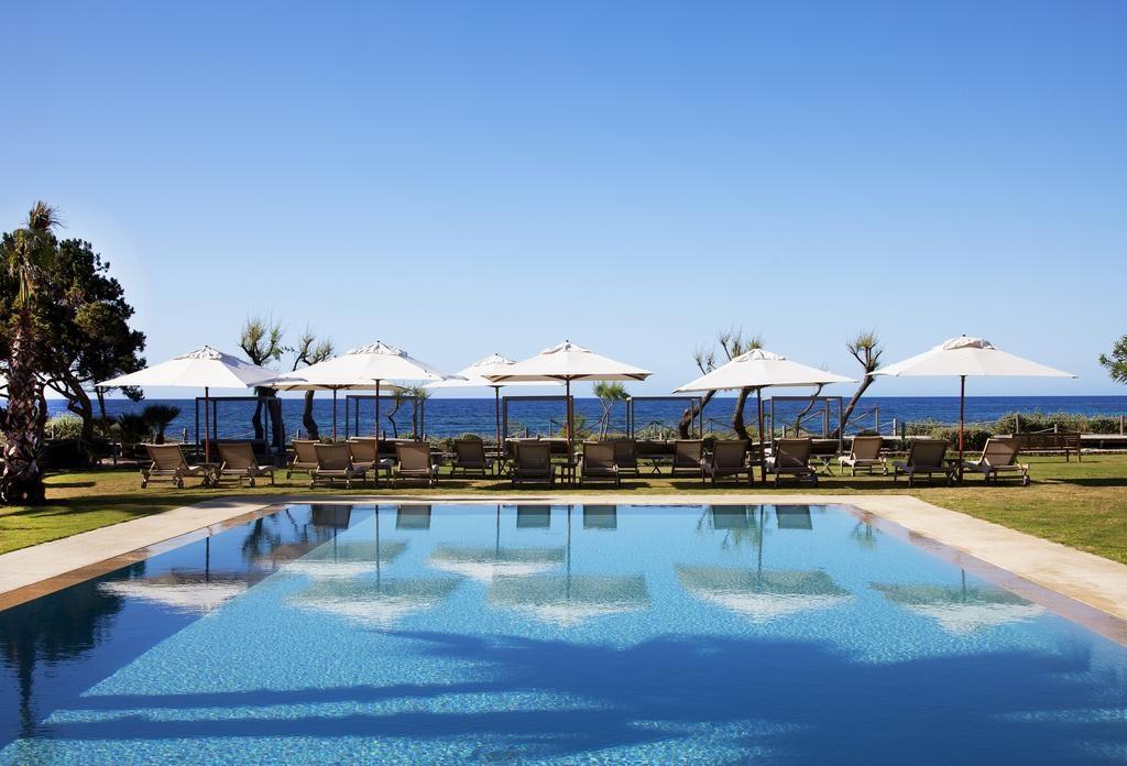 primer plano de piscina con hamacas y sombrillas al final, de fondo el mar y el cielo azul