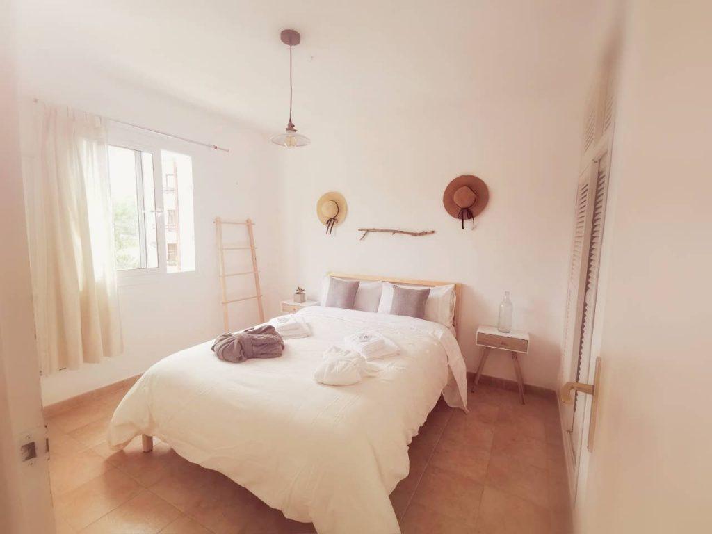 habitación interior cama sábanas blancas y cojines pared blanca cortina blanca suelo marrón