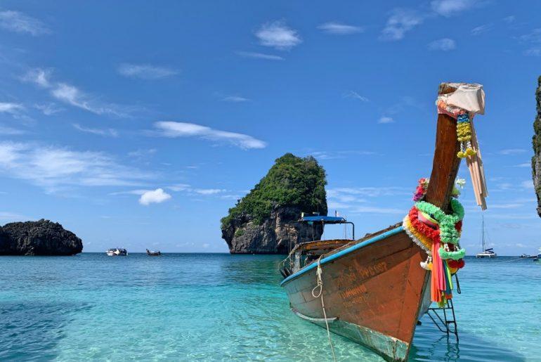 Cómo moverse por Tailandia en transporte público: barco de madera en aguas cristalinas.