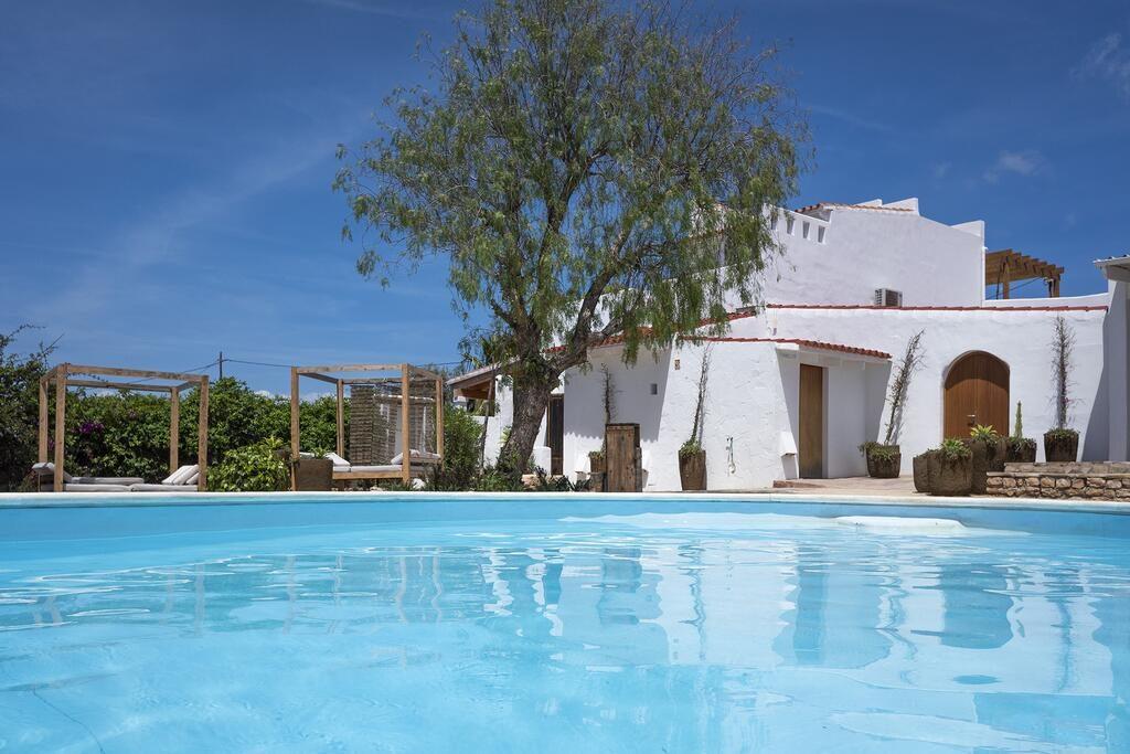 masía blanca al fondo junto con un árbol y naturaleza, piscina azul en primer plano, cielo azul al fondo