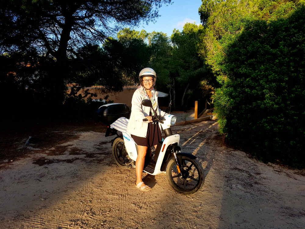 Carla sonriente con casco y chubasquero blanco vestido negro y sandalias subida en la moto eléctrica e-cooltra blanca en el camino del alojamiento al amanecer entre árboles
