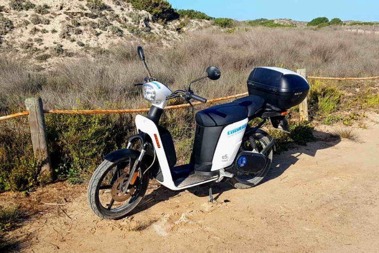 moto eléctrica e-cooltra blanca con baúl negro en un camino de playa con fondo vegetación cielo azul Formentera