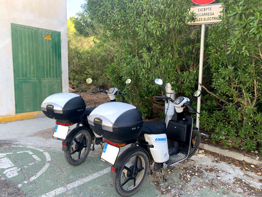 punto de recarga vehículos eléctricos dos motos eléctricas e-cooltra cargándose en el aparcamiento, fondo con vegetación y edificio de energía eléctrica